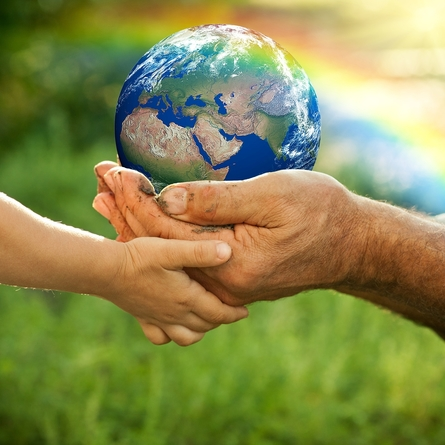 a small and a large hand holding the Earth together