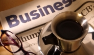 photo of a pair of glasses and a cup of coffee on a newspaper
